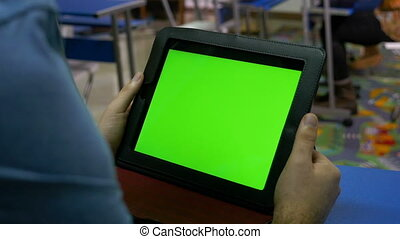Man holding a tablet pc with green screen in classroom
