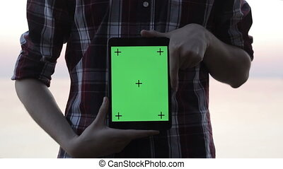 Man holding a tablet with a green screen