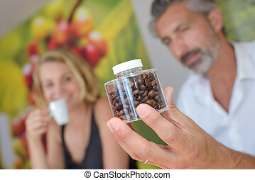 Man holding a transparent jar of coffee beans