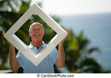 Man holding a white frame outdoors
