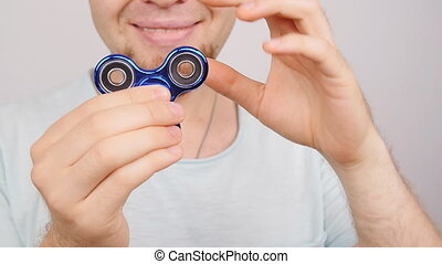 Man holding and playing with fidget spinner - Young man...