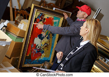 man holding and showing a painting to auctioneer before auction