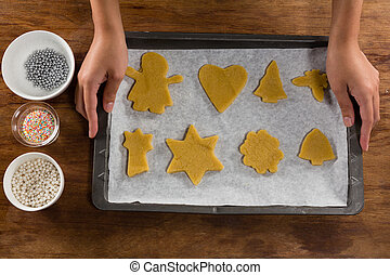 Man holding baking tray full of ginger bread cookies
