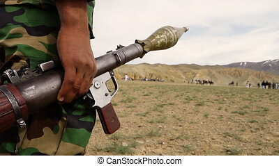 Man holding bazooka gun watches group of men play horse...