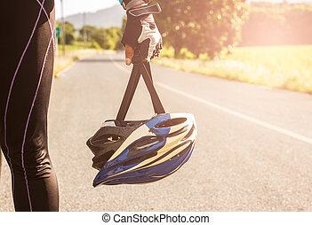 Man holding bicycle helmets prepare for cycling.