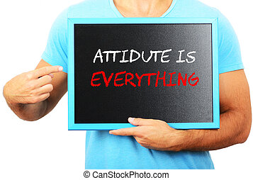 Man holding blackboard in hands and pointing the word ATTITUDE I