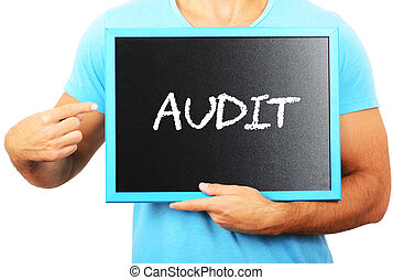 Man holding blackboard in hands and pointing the word AUDIT