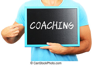 Man holding blackboard in hands and pointing the word COACHING