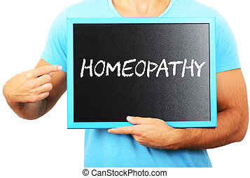 Man holding blackboard in hands and pointing the word HOMEOPATHY