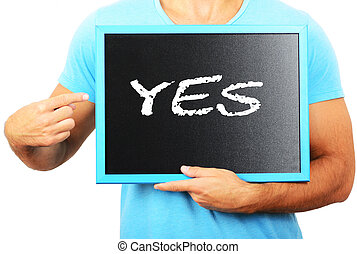 Man holding blackboard in hands and pointing the word YES