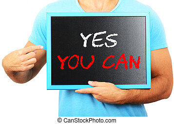Man holding blackboard in hands and pointing the word YES YOU CA