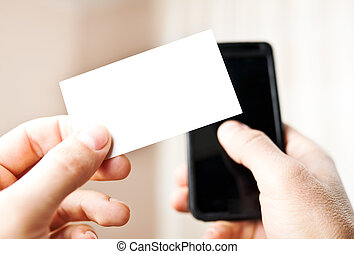 Man holding blank business card and dialing numbers on mobile phone