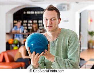 Man Holding Blue Bowling Ball in Club