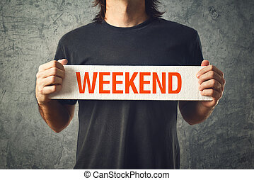 Man holding board with WEEKEND title