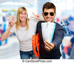 Man Holding Boarding Pass In Front Of Happy Woman Gesturing