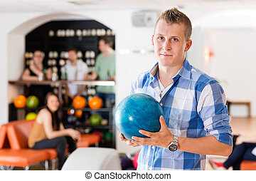 Man Holding Bowling Ball in Club