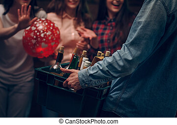 Man holding box with bottles of champagne at a party