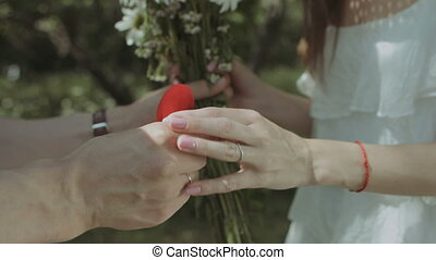 Man holding box with ring proposing to his girlfriend