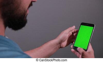 Man holding broken smartphone runs your fingers across screen
