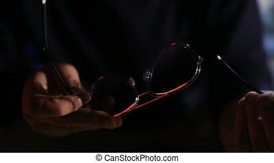 Man holding broken sunglasses in the dark room