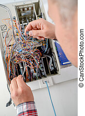 Man holding cables in electrical box