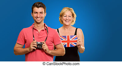 Man Holding Camera In Front Of Woman Holding British Flag
