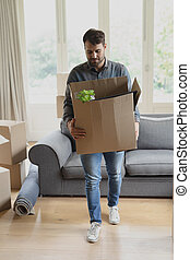 Man holding cardboard box in new home