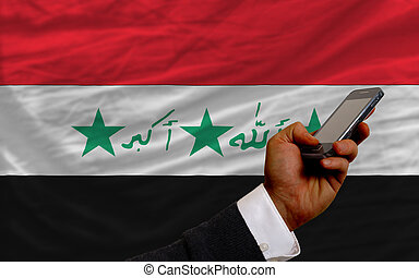 cell phone in front national flag of iraq