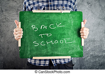 Man holding chalkboard, back to school