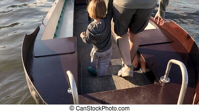 Man holding child by hand walking on boat - Back view of...