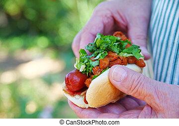 Man holding chili dog outdoors