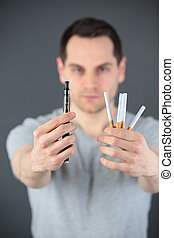 man holding cigarettes and electronic cigarette