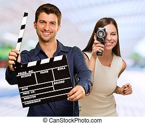 Man Holding Clapper Board And Woman Capturing Photo - Man...