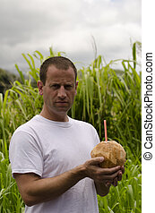 Man holding coconut.