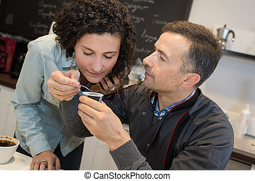 Man holding coffee for woman to smell