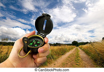 man holding compass in field - man navigating along a...