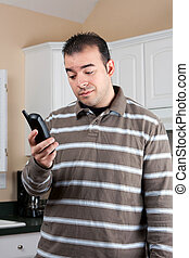 Man Holding Cordless Phone - Young man holding a cordless...