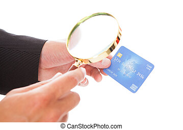 Man Holding Credit Card And Magnifying Glass - Close-up Of...
