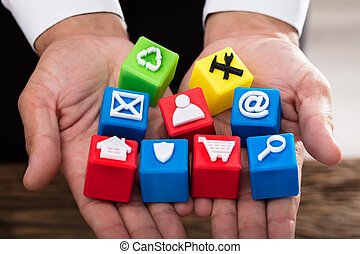 Man holding cubic blocks with vivid icons
