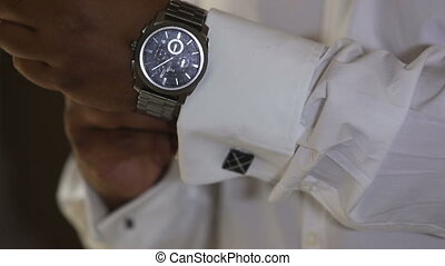 man holding cuffs in the sleeve white shirt