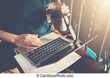 Man holding cup of coffee in hand and working with laptop. Generic design laptop is on his knees. Sunlights effects