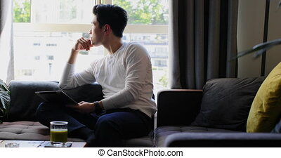 Man holding digital tab in looking out from window 4k
