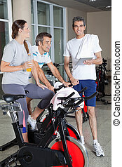 Man Holding Digital Tablet While Friends Exercising On Spinning