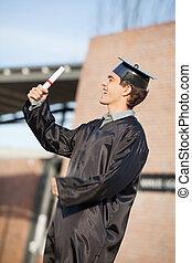 Man Holding Diploma On Graduation Day At Campus