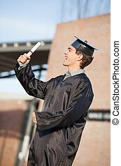 Man Holding Diploma On Graduation Day At Campus