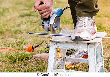 Man holding electric angle grinder and cutting metal, sparks from tool.