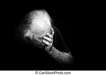 Gritty black and white image of older man holding head in despair, grain added to make more dramatic.