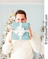 Man holding gift box in front of his face