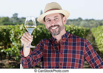 man holding glass-of-wine while staring happily at the camera