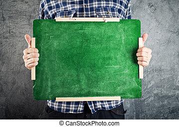 Man holding green chalkboard. Empty classroom blackboard for your text.
